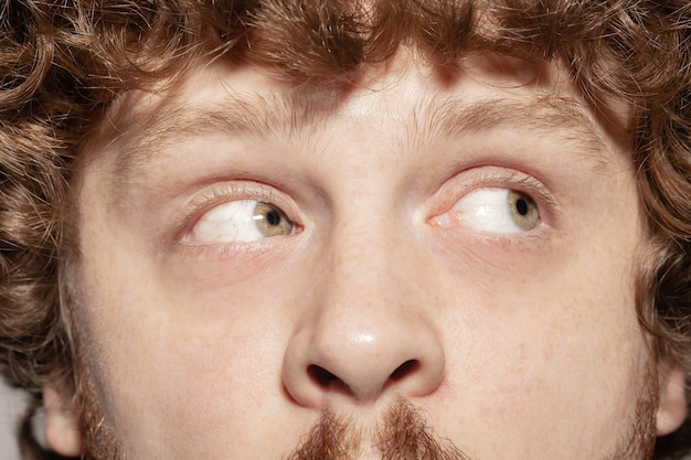 Asking at side. close up of face of beautiful caucasian young man, focus on eyes.