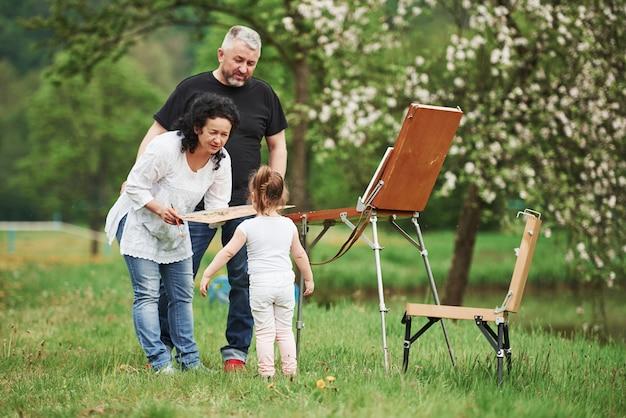 Chiedere una prova. nonna e nonno si divertono all'aperto con la nipote. concezione della pittura