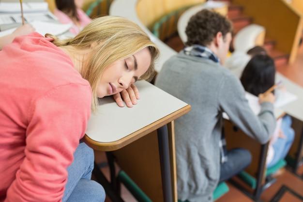 강당에 앉아있는 학생들과 자고있는 여성