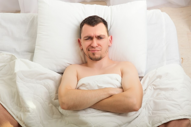 Asleep man lying in bed.