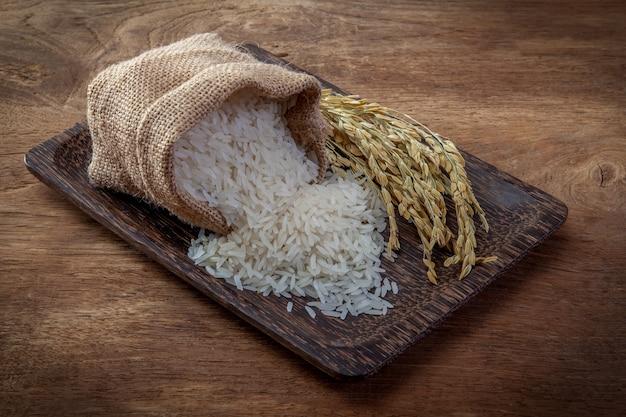 Asmine white rice in small burlap sack on wood