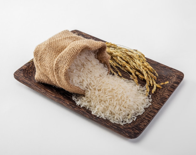 Asmine white rice in small burlap sack on wood