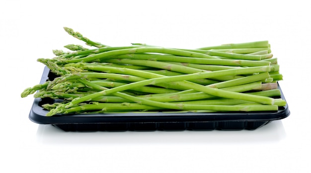 Asparagus in black plastic tray on a white background