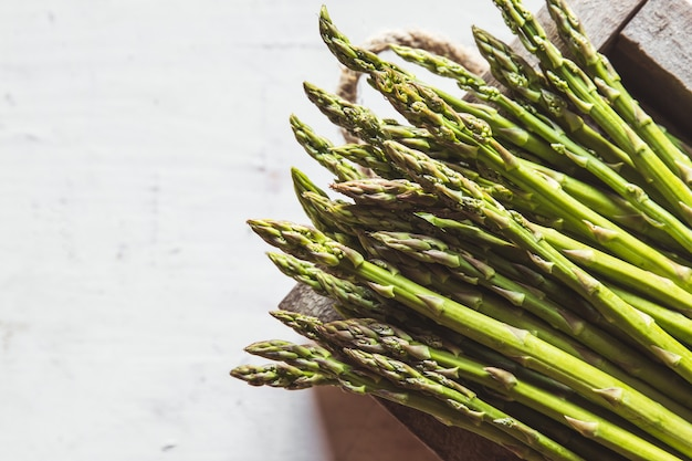 Asparagus on a cut board on an old white background