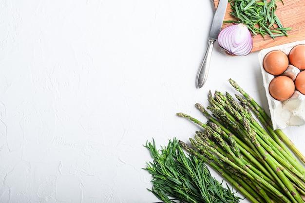 Яйца спаржи и французские ингредиенты для заправки с дижонской горчицей, лук, нарезанный тарагоном красного уксуса на белом текстурированном фоне, вид сверху с пространством для текста.