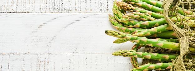 아스파라거스. 흰색 오래된 나무 배경에서 요리할 준비가 된 신선한 녹색 아스파라거스 무리. 상위 뷰 복사 공간입니다.