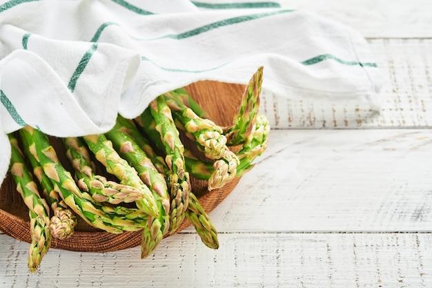 アスパラガス。新鮮なグリーン アスパラガスの束は、白い古い木製の背景で調理する準備ができています。トップ ビュー コピー スペース。