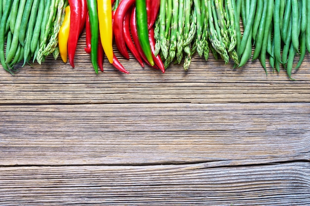 Asparagus, green beans and colorful chilli pepper on rustic wooden background