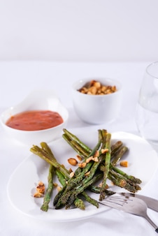 Asparagus roasted in olive oil with crushed walnuts and sauce on a white plate. vegetarian food.