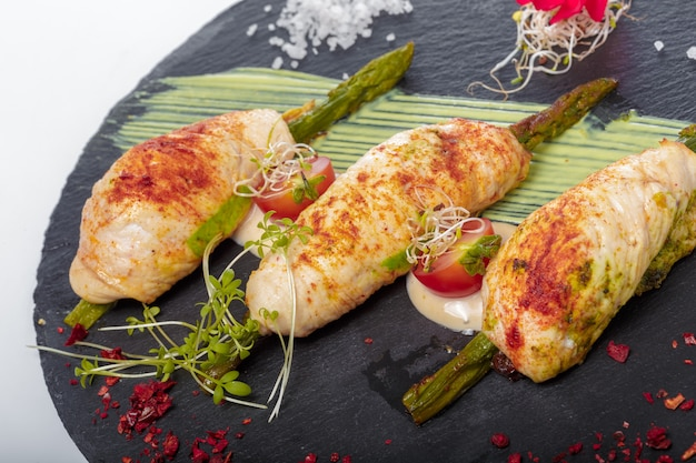 Asparagus rolled in grilled bacon served with sauce on dark plate
