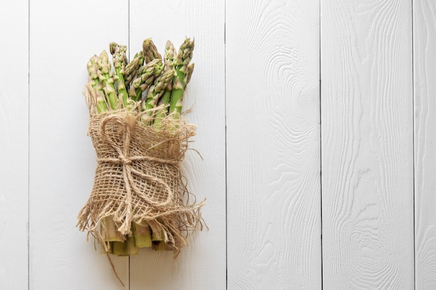 Asparagus shoots are tied with a jute rope on white boards. fresh asparagus is wrapped with a jute cloth on a white wooden background with a copy of space.