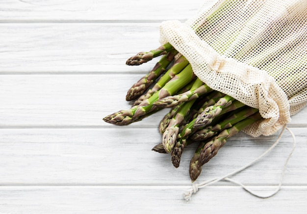 Asparagus stems in an eco mesh bag on a old wooden surface