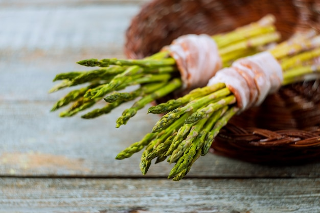 Asparagus with rolled in bacon, on a wooden background, rustic style