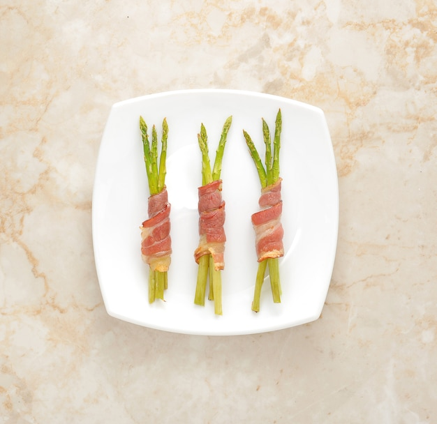 Asparagus wrapped in bacon on a platter