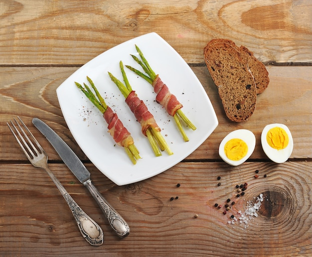 Спаржа в беконе на блюде и яйцо