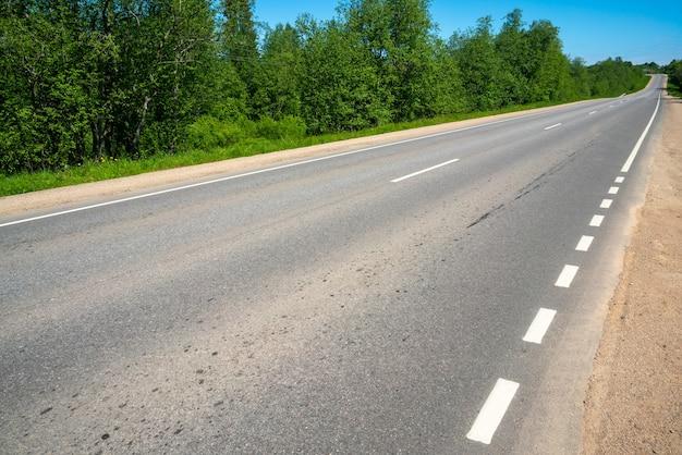 アスファルト田舎道。道路標示。夏の晴れた日。
