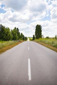 농촌 분야 사이의 아스팔트 평평한 도로. 여름, 화창한 날, 아름다운 하늘.