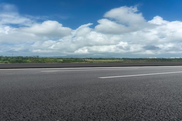 Асфальтовая земля и голубое небо с белыми облаками
