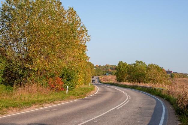 コテージのある美しい秋の丘に囲まれたアスファルト高速道路の田舎道。