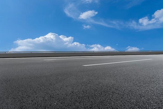 アスファルト高速道路のスカイラインと青い空と白い雲