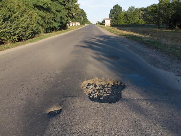 大きな甌穴のある踏切近くのアスファルト。修理が必要な損傷した道路。