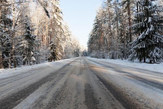 Асфальтовая часть дороги под снегом после снегопада, небо в центре кадра, дорога проложена через лес, покрытый сугробами и снегом
