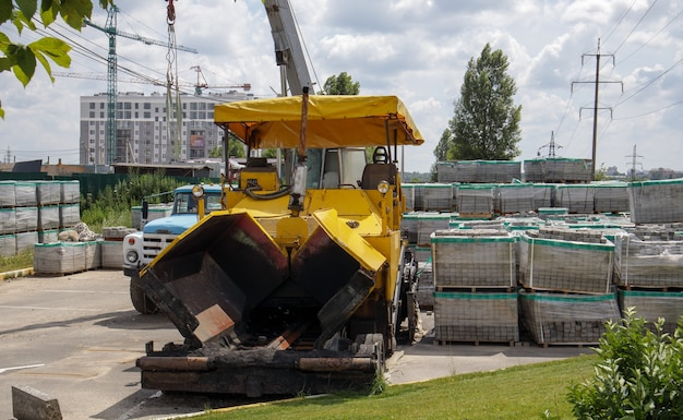 An asphalt paver is parked at a construction site. road construction machinery stands by the road in a warehouse. construction of heavy roads and repair of city streets.