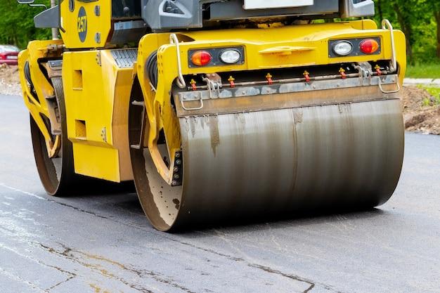 アスファルト締固め中の道路上のアスファルトペーバーがクローズアップ。道路の修理。新しい道を築く