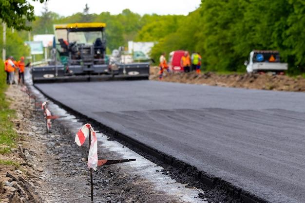 焦点がぼけたアスファルト敷設中の道路上のアスファルトペーバー。道路の修理。新しい道を築く