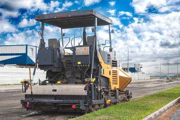 Оборудование для укладки асфальта. асфальтоукладчик и тяжелый вибрационный каток. строительство новых дорог и дорожных развязок. тяжелая строительная промышленная техника.