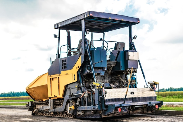 Asphalt paving equipment. asphalt paver and heavy vibratory roller. construction of new roads and road junctions. heavy construction industrial machinery.