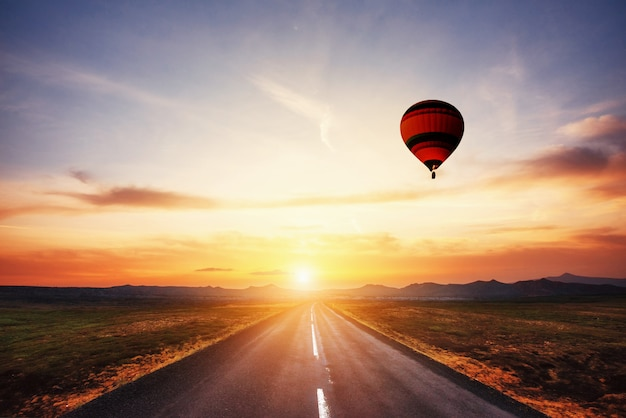 Asphalt road along and colored ball in the sky at sunset