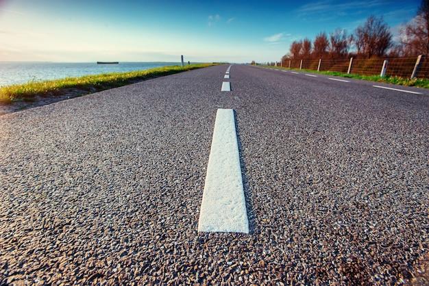 Asphalt road along the sea in a fantastic summer day