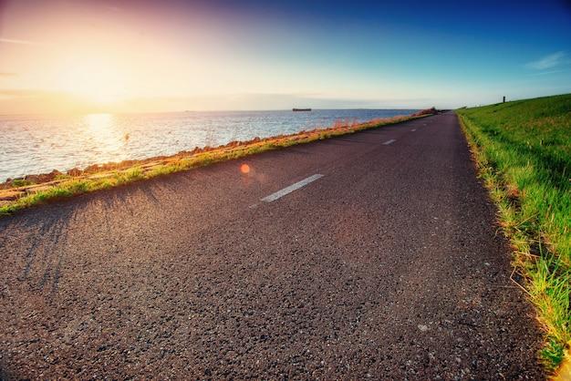Asphalt road along the sea at sunset