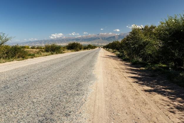 キルギスタンのイシククル湖の南岸に沿ったアスファルト道路。