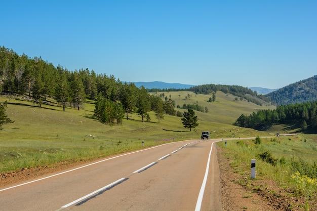 대초원과 언덕 사이의 아스팔트 도로.