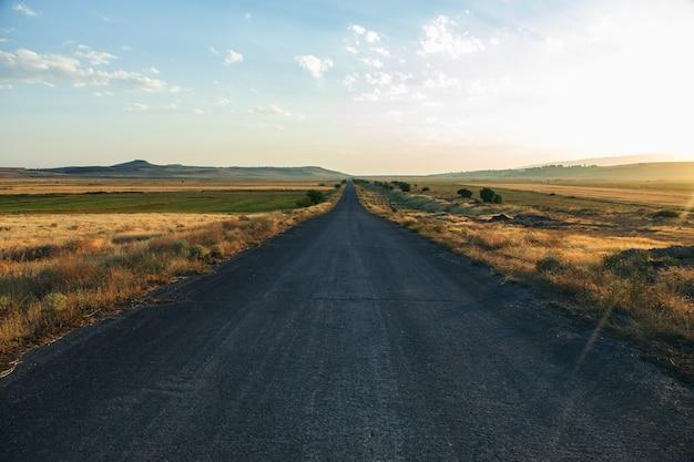 Асфальтовая дорога и поле на закате