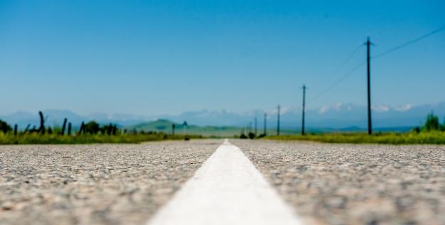 Асфальтированная дорога и зеленые поля с горами под голубым небом