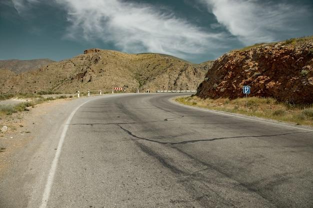 Асфальтовая дорога и скалы на фоне неба