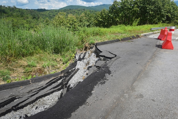 Asphalt road collapsed and cracks in the roadside - road landslide subside with plastic barriers on uphill