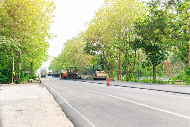 Asphalt road construction with machine and steamroller truck at freeway in thailand.