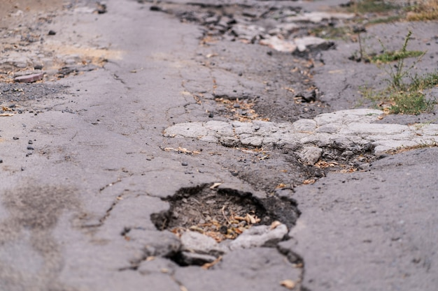 Asphalt road destroyed by holes and washed out by water