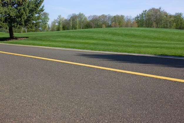공원의 녹색 잔디를 통해 자전거와 보행자를위한 아스팔트 도로