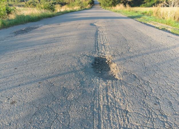 甌穴と甌穴のある状態の悪いアスファルト道路