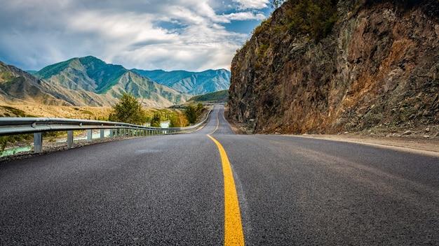 아스팔트 도로. 완벽한 아스팔트가 있는 아름다운 산길이 있는 풍경. 높은 바위, 여름 일몰의 놀라운 하늘. 파노라마. 여행 배경입니다. 산에서 고속도로