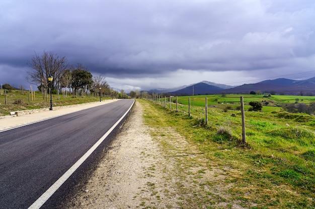 어두운 폭풍 구름 하늘 산으로 이어지는 아스팔트 도로. 마드리드.