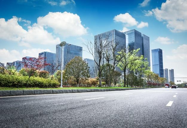 Asphalt road and modern city Free Photo