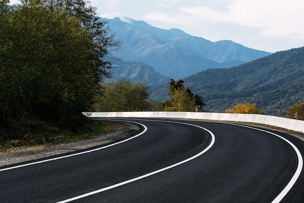 아스팔트 도로. 산의 배경에 포장된도. 코카서스의 아름다운 산을 배경으로 하는 도로. 국가의 풍경입니다. 자동차로 아름다운 곳을 여행하십시오. 복사 공간