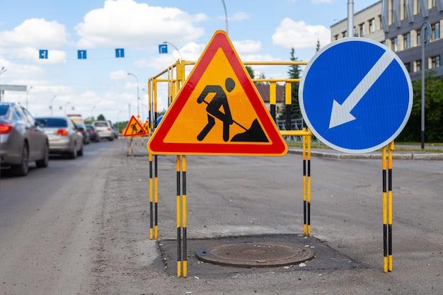 アスファルト道路は、道路工事とバイパスの方向についての黄色の三角標識を修復します