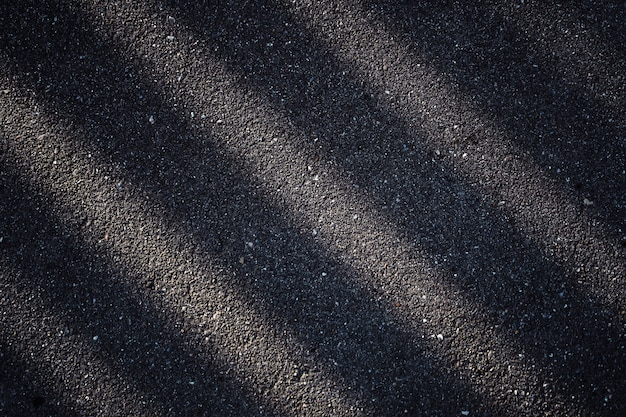Asphalt road with a dark shadow of the fence. abstract stripes are light and dark.